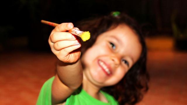 Child holding and pointing forward a paintbrush