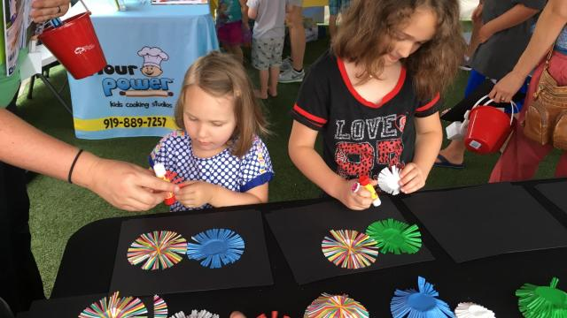 Kids make a fireworks craft, provided by Select Sitters, at Go Ask Mom's North Hills event.
