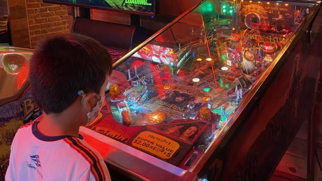 My friends' son enjoys pinball while wearing his mask at Bowstring Pizza and Brewyard in Raleigh this July.