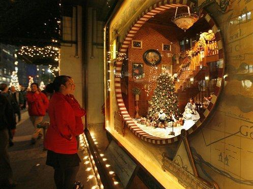 Two employees of Lord & Taylor's flagship Fifth Avenue store pause to admire the store's elaborate Christmas window display in New York, in this Wednesday, Nov. 14, 2007 file photo. The elaborate window displays are constructed in the basement and then lifted into position for display to the public. (AP Photo/Kathy Willens, FILE)