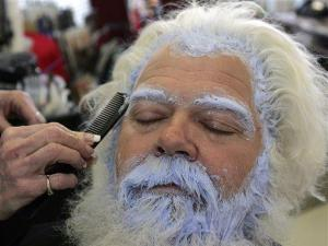 Mall santa Dana Craven gets his eyebrows and the roots of his beard retouched by stylist Joyce Beisel, hand shown, in Roswell, Ga., Thursday, Dec. 6, 2007. (AP Photo/John Bazemore)