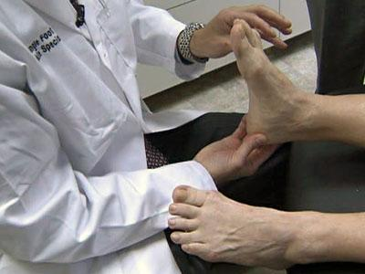 Podiatrist Dr. Jeremy Thomas, with Triangle Foot and Ankle, examines Cherrel Cortopassi's feet.