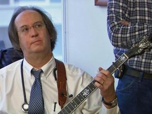 David Tate, a cardiologist at UNC Hospitals, picks his banjo – signed by legendary Earl Scruggs – as part of the band Fescue 911. He also puts on impromptu concerts for patients to lift their spirits.