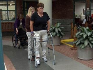 Debbie Myers works with a walker at WakeMed's spinal cord injury rehabilitation center 10 years after a fall left her paralyzed.
