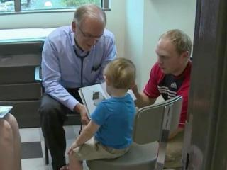 Dr. Thomas Flaherty checks on the reading progress of Xander Sevier while his parents, Noah and Elisa Sevier look on.