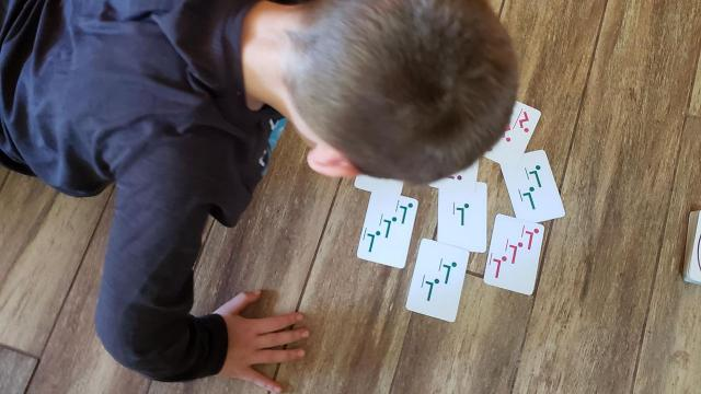 Dan DeJager created Super Fitness Fun Cards to help his students stay stay active in the pandemic. His son Hunter, 10, does push-ups while playing with a deck.