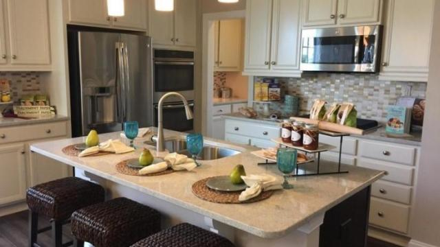 the cream coloring of the cabinetry and countertops and soft pastel accent pieces work well with their theme as well as the basket woven bar stools and - How To Decorate Your House