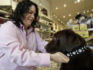 Alice Lerman, owner of high-end pet store Barker & Meowsky, tries a $250 custom-made, crystal-encrusted dog collar made from python skins on her dog Gus Friday, Nov. 9, 2007, in Chicago. U.S. retail sales may be weak, energy prices way up and housing prices way down, but experts say pets largely defy such economic indicators. Caring owners are no more likely to stiff their beloved animals for the holidays than Santa is to leave rocks in every stocking. (AP Photo/M. Spencer Green)