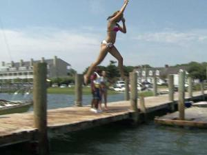 A girl takes a leap from a dock on the Beaufort Inlet along North Carolina's Crystal Coast. Beaufort's quaint, historic waterfront is a major attraction for visitors.