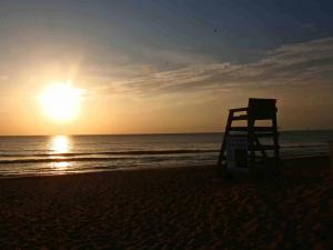 The sun rises between a lifeguard stand and deck in Kitty Hawk.