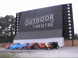Classic cars park in front of the screen tower of Jim Kopp's Raleigh Road Outdoor Theatre.
