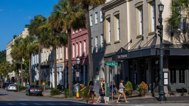 """People walk past the Vendue, a hotel in Charleston, S.C., July 16, 2020. A powerful visitors' bureau has pushed Charleston to the top of """"best"""" lists by selling gentility, but critics say that has come at the expense of history and the city's Black population. (Hunter McRae/The New York Times)"""