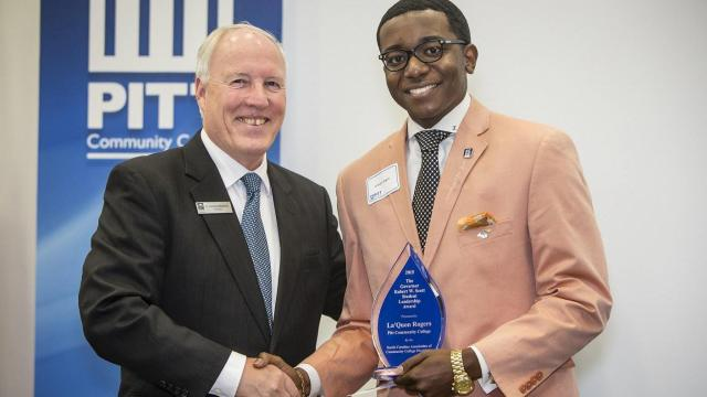 La'Quon Rogers (right) accepts the Governor Robert W. Scott Student Leadership Award from the North Carolina Association of Community College Presidents.