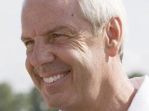 UNC Coach Roy Williams smiles for cameras after signing more autographs.