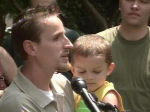 Tim Nielsen and his 3-year-old son Skylar talk to reporters Friday about a $10,000 reward being offered to catch his slain wife's killer. Jenna Nielsen was stabbed to death in the early morning hours of June 14. Her body was found behind a Raleigh convenience store.