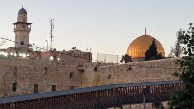 The Western Wall, a minaret and the Dome of the Rock at dusk.