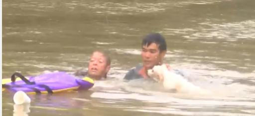 A man jumps into flood waters to save a woman and her dog from a sinking car. (Deseret Photo)
