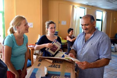 Volunteers and refugees sort through book donations shipped to the Kyllini refugee camp in western Greece in July 2016. (Deseret Photo)