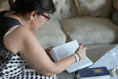 Stavroula Dimarhopoulou, 50, searches for a verse in the Bible to explain how faith motivated her family to take in two families of refugees at her home in Nikopolis, Greece, July 17, 2016. (Deseret Photo)