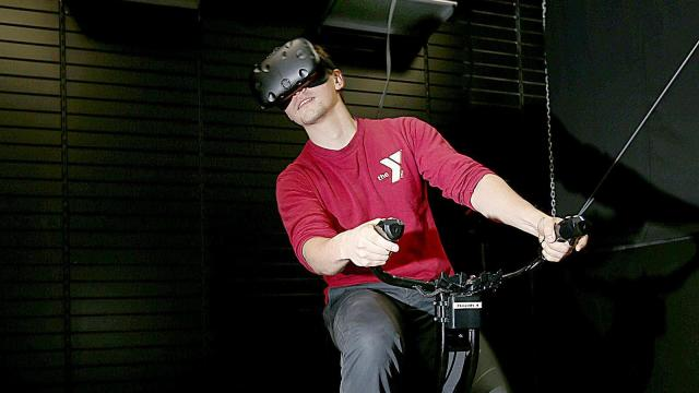 """Jonathan Krone of Dallas drives a race car while playing """"Vir Zoom"""" at VR Junkies at the Valley Fair Mall in West Valley on Friday, Feb. 3, 2017. The faster Krone pedaled the bicycle the faster the car went. (Deseret Photo)"""