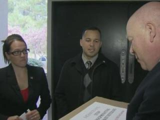 Kevin Fitzgerald, chief of staff for the University of North Carolina System, accepts a box of petitions from Hayleigh Perez, an Iraq War veteran from Raeford who was denied in-state tuition.