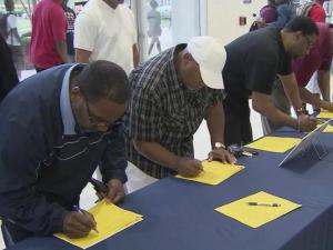 Fathers sign up on Aug. 26, 2013, to be volunteers at Hillside High School in Durham as part of Million Fathers March, a nationwide movement to get them to be more active in their children's schooling.