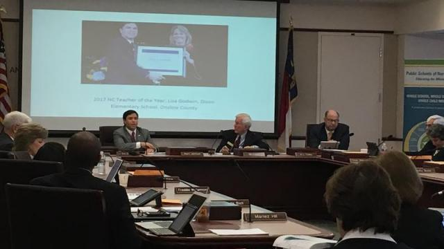 State Board of Education Chairman Bill Cobey (center-right) listens while State Superintendent Mark Johnson gives his monthly address to the board.
