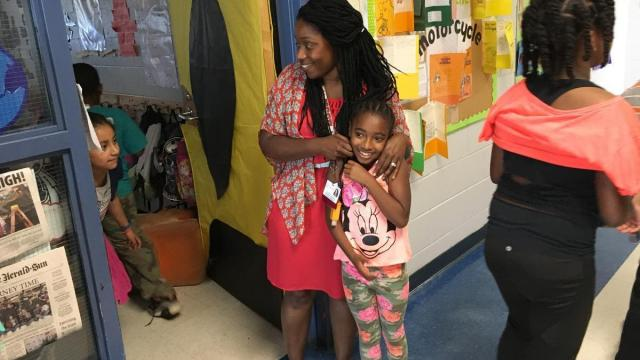 Eastway third-grade teacher Turquoise LeJeune Parker gives her student DeAsiah a hug before her class heads off for lunch. Parker's students take their first end-of-grade test this year. Photo by: Jess Clark / WUNC