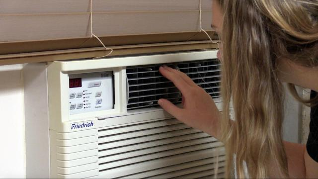 Emili Potts examines the window air conditioning unit of her room in Craige dorm on the UNC-Chapel Hill campus. (Photo UNC/Hayley Boland)