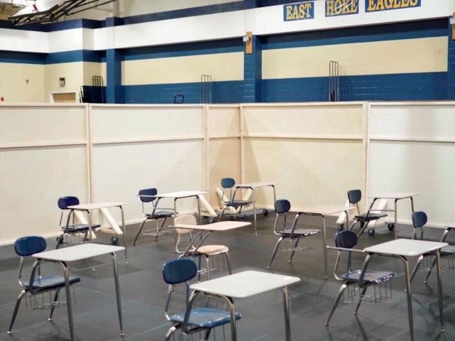 At East Hoke Middle School, the cafeteria has been divided into temporary classrooms, with desks spaced six feet apart.