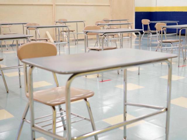 In the classroom in Fall 2020, desks are removed and others spread out to allow for social distance.