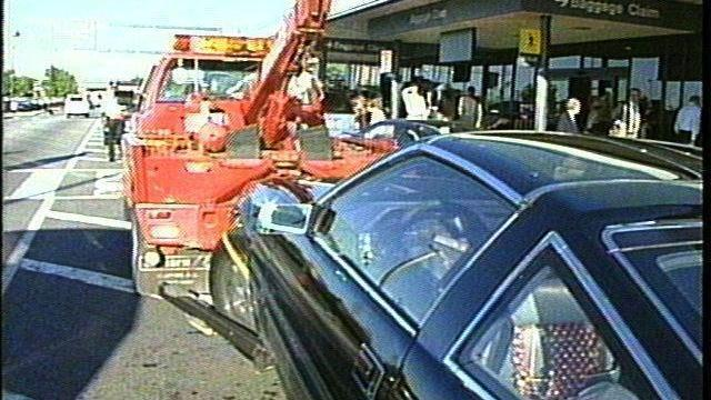 A tow truck moves a 280ZX from a no parking zone at the RDU Airport. (WRAL-TV)