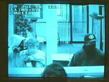 Surveillance tape from Centura Bank shows the two robbers, one of them holding a gun to a bank customer's head. (WRAL-TV5 News)