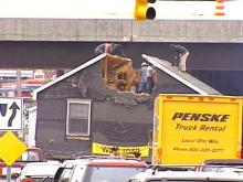 As traffic backed up, the house movers took chainsaws in hand to get under the overpass.(WRAL-TV5 News)