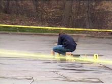An investigator collects evidence in the parking lot at the Woodcreek Apartments.(WRAL-TV5 News)