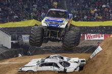 """T-Maxx"" flies over the piled up cars as he finishes a qualifying race."