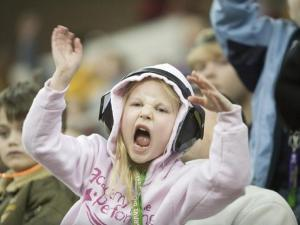 A young monster truck fan gets excited while cheering for the trucks.
