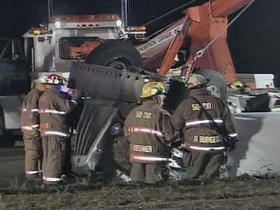 Emergency personnel worked at the scene of a collision that killed at least one person inside a tractor-trailer.