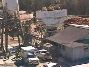 Rescue crews try to extricate the body of a man killed when a pile of sand at a concrete company collapsed on him.