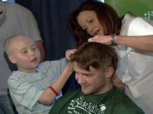 Carolina Hurricanes goalie Cam Ward gets a haircut from a fan Friday evening at the Hibernian Restaurant and Pub in Cary. Ward went bald to help raise money for childhood cancer research.
