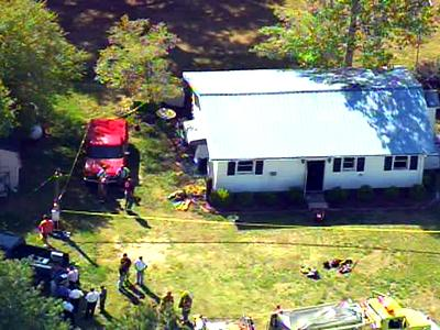 Firefighters gather outside a house where they found one person dead when they responded to a house fire on Monday, April 23, 2007.