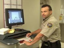 CCBI Agent Andy Parker explains the process for fingerprinting, which takes about three minutes under the new system. Under the traditional ink-and-pad method, agents spent about 10 minutes taking prints.