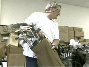 A volunteer with Give2TheTroops organizes golf clubs.