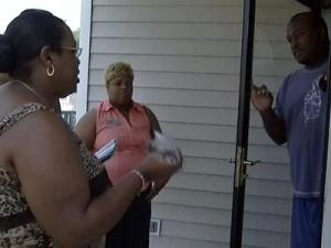 Darlette McCormick and Brenda Allison talk to a man Wednesday about how to avoid house foreclosures.