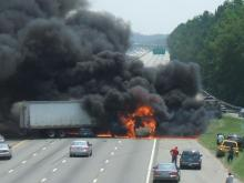 Firefighters douse the flames that consumed a tractor-trailer that wrecked on Interstate 40 near the Raleigh-Durham International Airport.