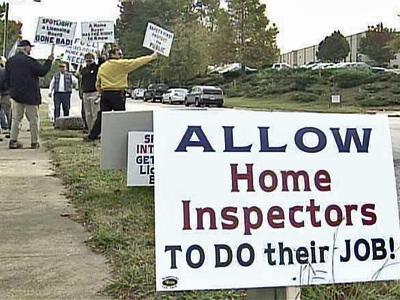 Home inspectors protest outside a meeting of the Home Inspector Licensure Board, which voted Friday to delay a decision on a proposal that would limit what home inspectors can put in their reports.