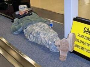 A member of the Texas National Guard, temporarily stationed at Fort Bragg, sleeps at RDU while awaiting a Southwest Airlines flight home for the holidays. (Photo by John Lucy)