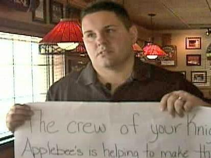 Applebee's Manager Keith Brozzoski holds up a sign the restaurant created when it heard about the family's struggle after the fire.