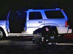 A trooper takes measurements near the SUV the 16-year-old boy was driving when he accidentally hit his step-sister Monday evening.