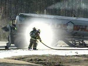 Firefighters clean off a tanker that overturned and spilled about 4,500 gallons of gasoline on March 5.